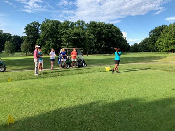 Tekoa Gamble learning golf as part of Gross Mendelsohn's women's initiative